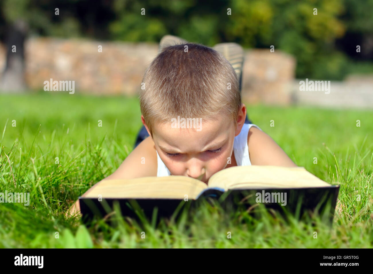 Kind liest Buch Stockbild