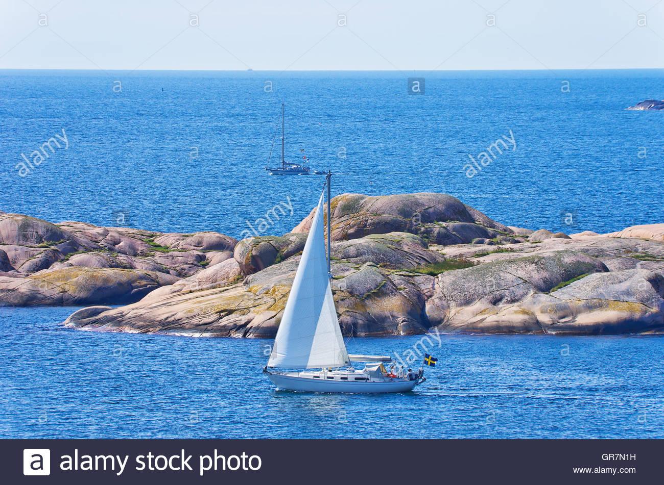 Ein Segelboot geht vorbei an einer Schäre vor der Küste von Lysekil, Bohuslan, Schweden. Stockbild