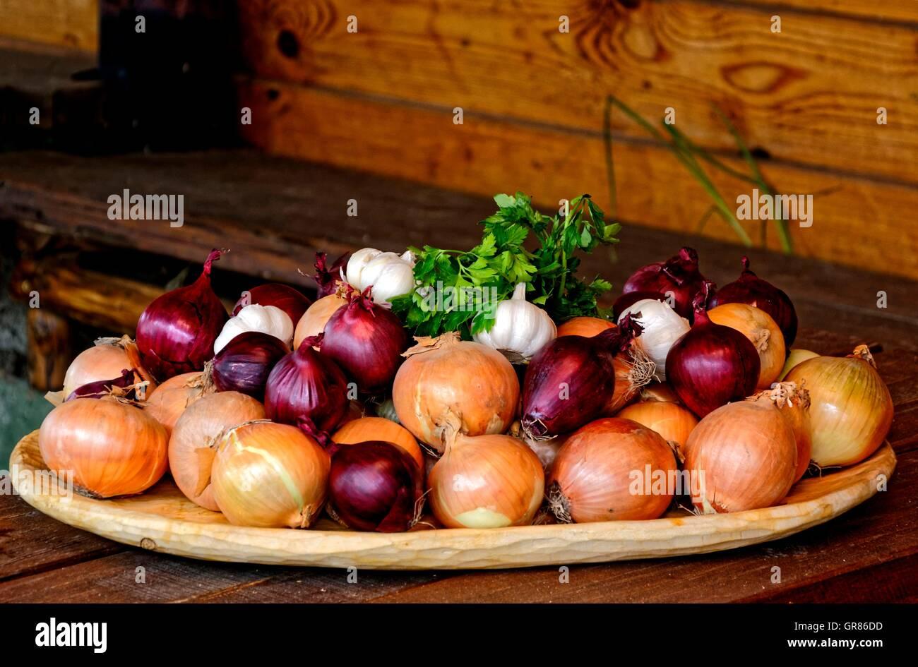 Zwiebel, Allium Cepa, Sorten auf Holzplatte Stockbild