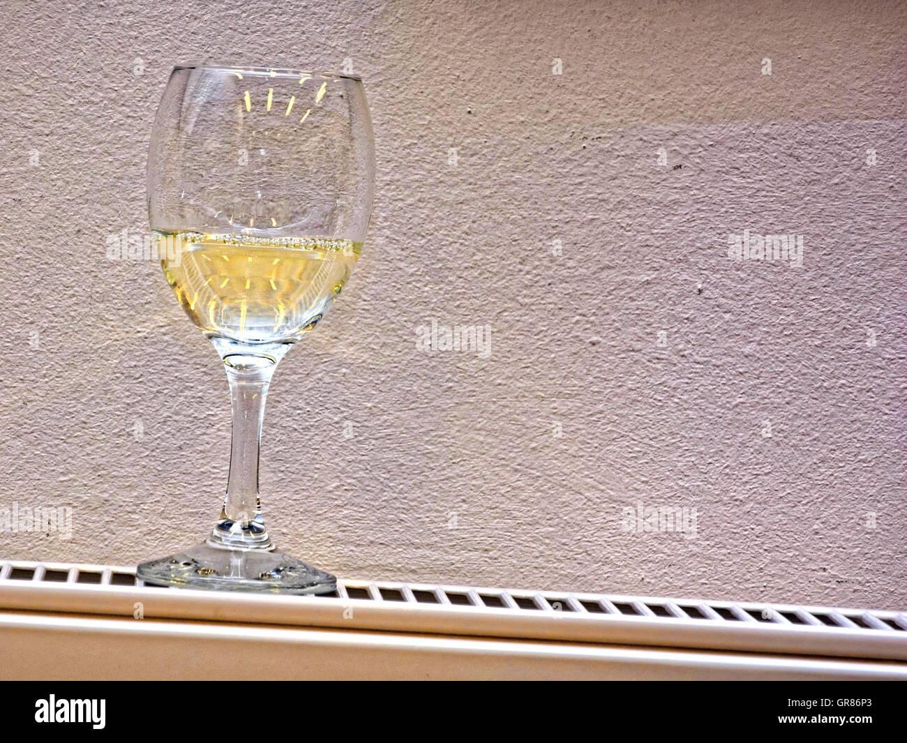Weinglas mit Weißwein auf geneigten Heizkörper, Heizkörper Stockbild