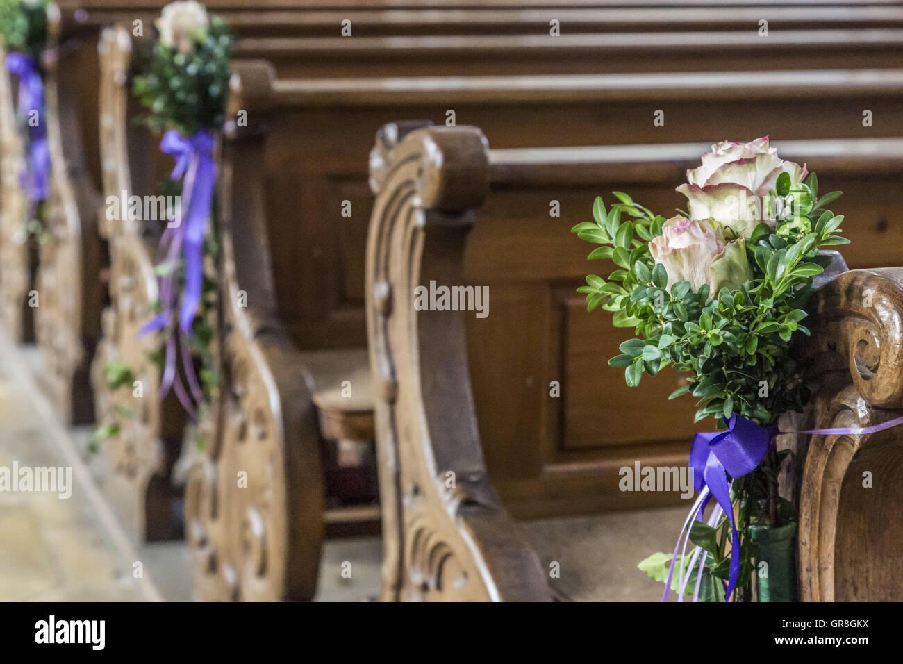 Detailansicht einer alten Holzbank In einer Kirche mit einem Blumenschmuck Stockbild