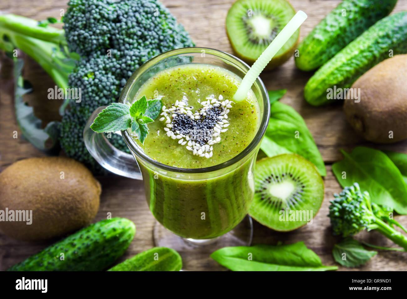 Grüne Gemüse und Kräuter Smoothie mit Herz aus Mohn und Sesam. Liebe für eine gesunde Rohkost Stockbild