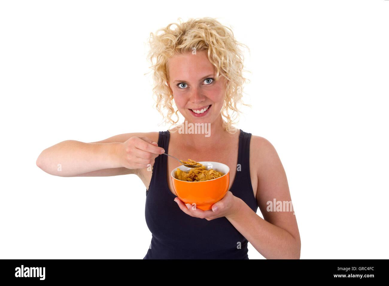Junge Frau aus einer Schüssel Cornflakes zu essen Stockbild