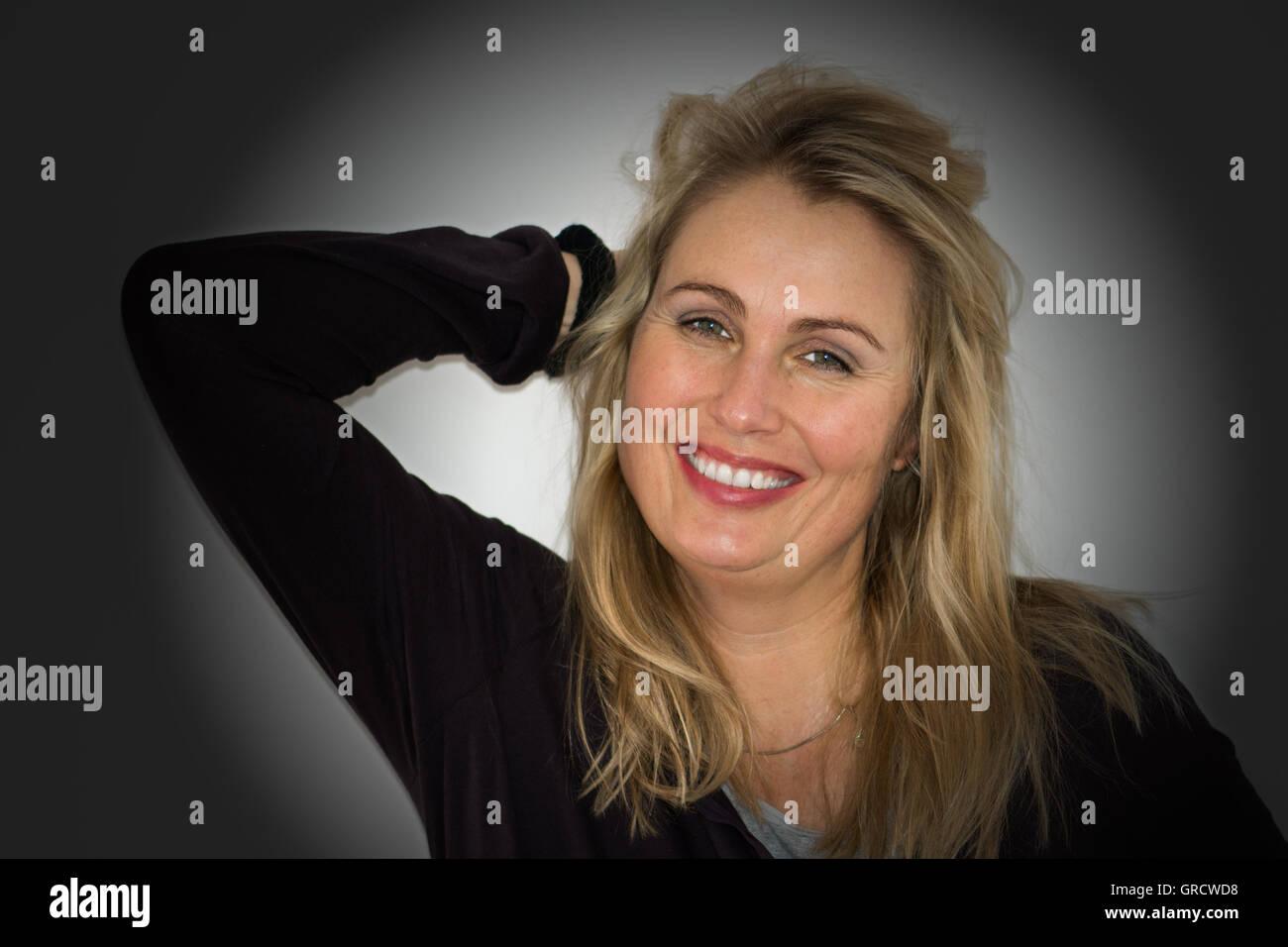 Porträt einer hübsche blonde Frau lachend in die Kamera, Studioaufnahme Stockbild