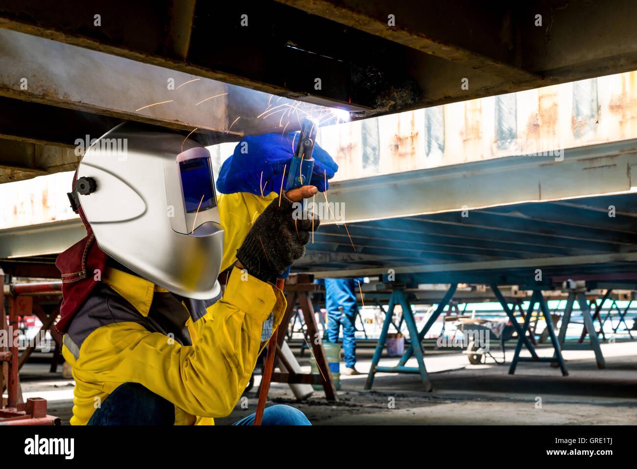 Arbeiter reparieren die Schäden Unterseite der Container, Industrie, Fabrik, Schweißen closeup Stockbild
