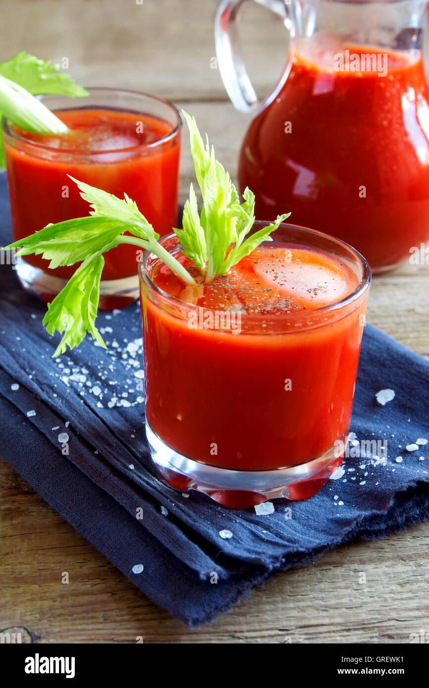 Tomatensaft mit Sellerie, Gewürzen, Salz und Eis in Gläser Teil. Bloody Mary cocktail. Stockbild
