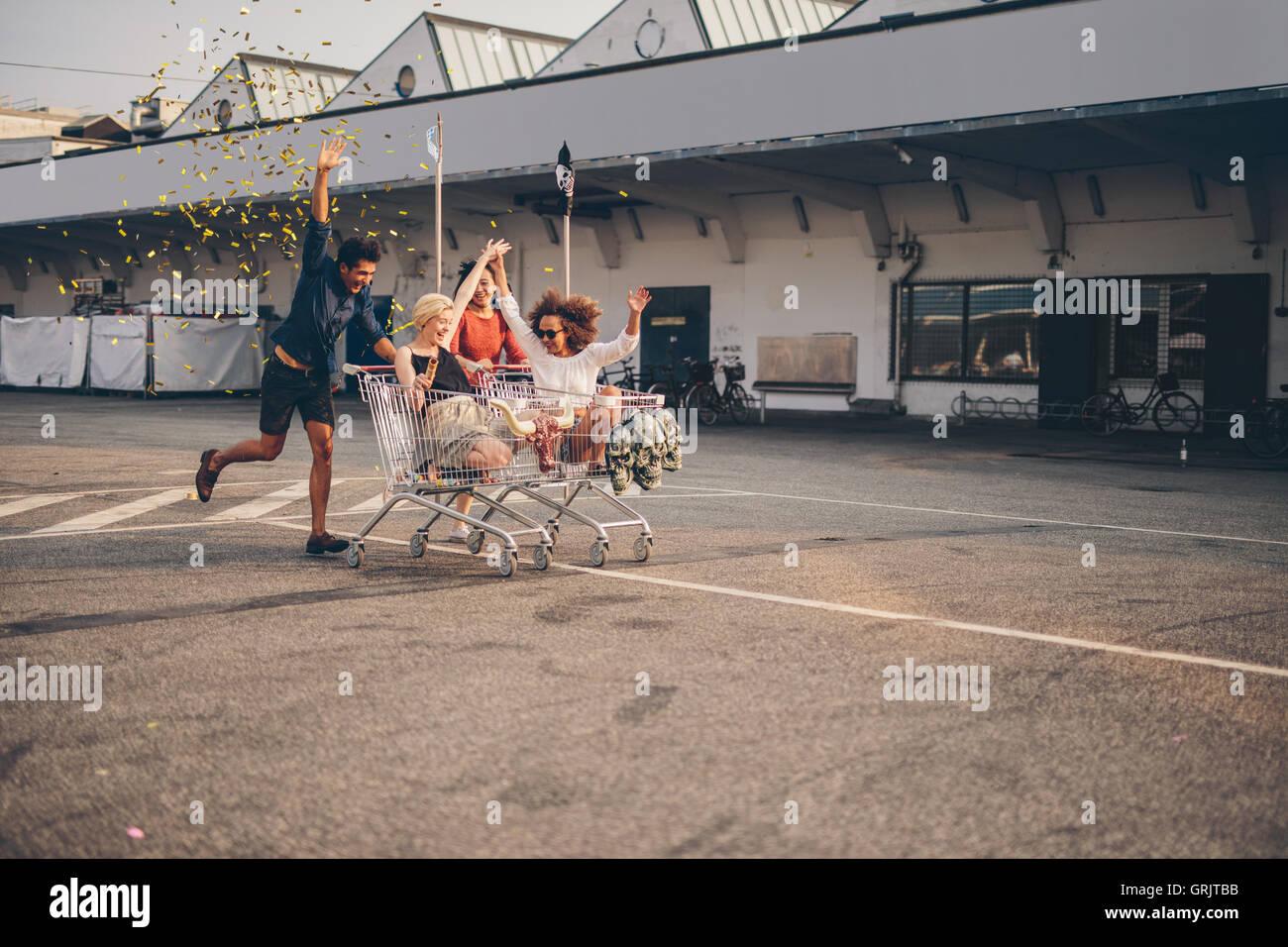 Junge Freunde, die Spaß am Einkaufswagen und Konfetti weht. Multiethnische Jugendlichen racing mit Einkaufswagen Stockfoto
