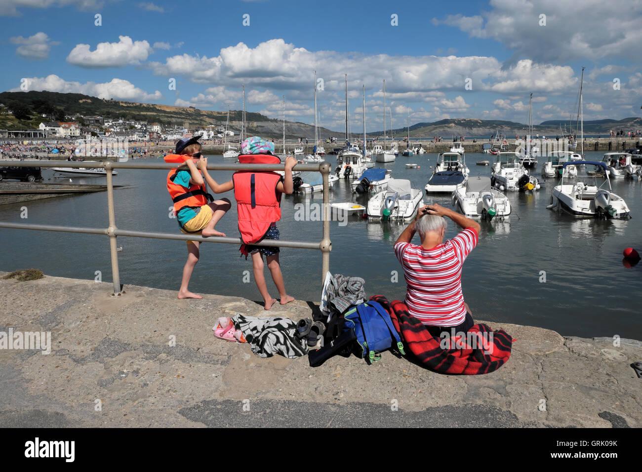 Eine Großmutter und zwei Enkelkinder sitzen am Hafen Kai entlang der Cobb bei Lyme Regis Dorset England UK KATHY DEWITT Stockfoto