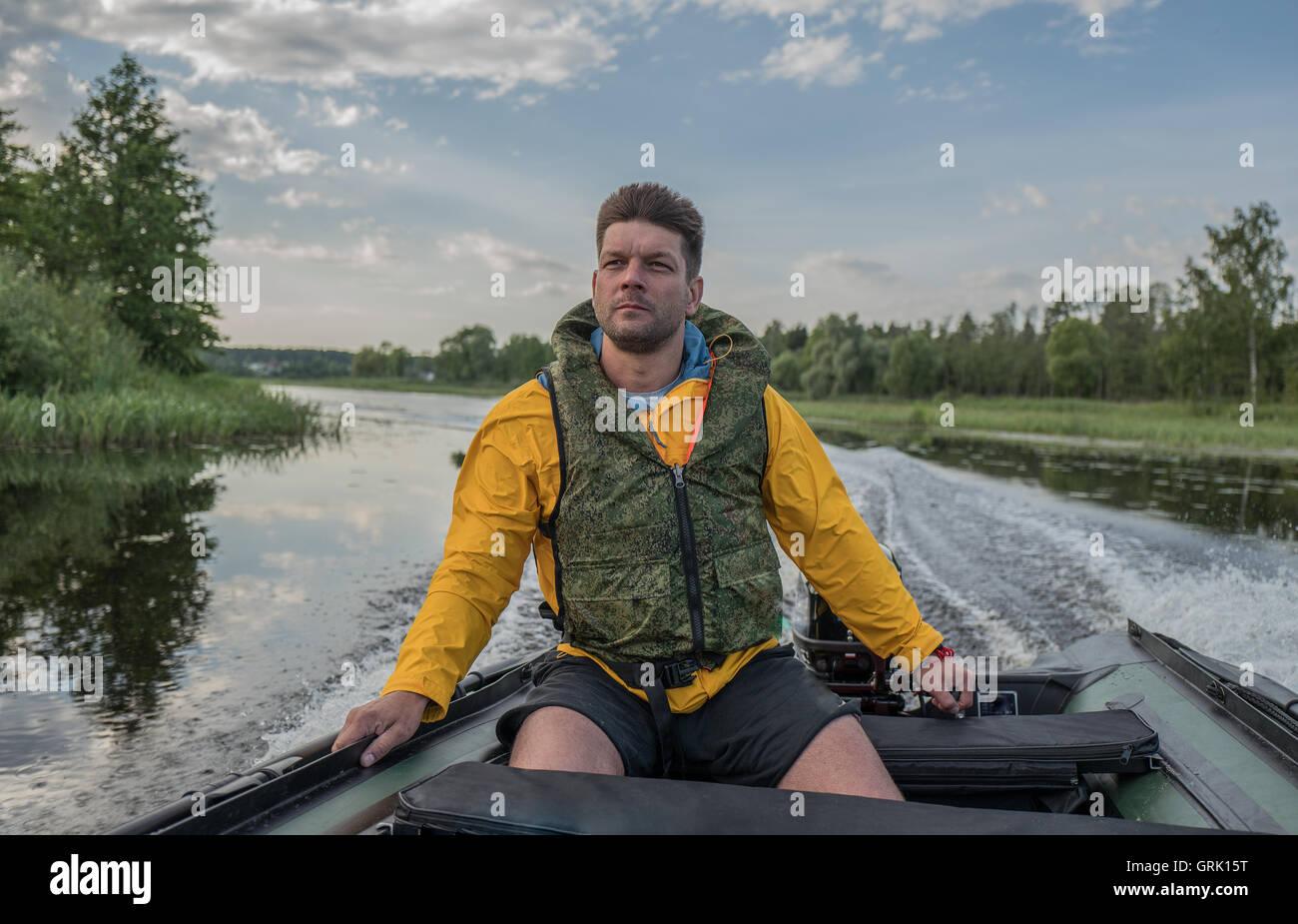 Mutigen gutaussehenden Mann ist der Boot auf dem Fluss Stockbild