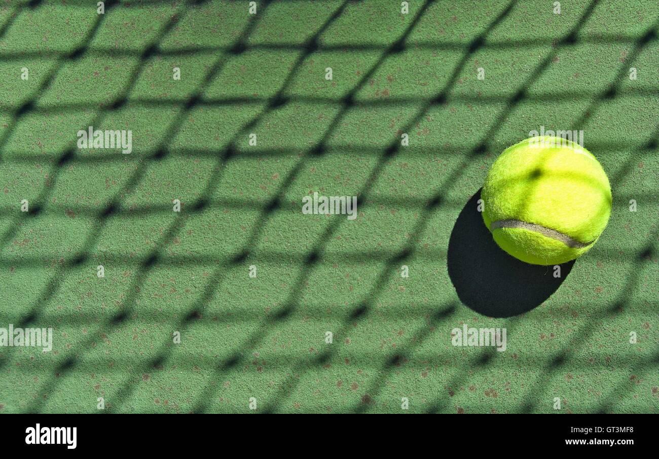Kreuz und quer net Schatten auf Neon Tennisball. Stockbild
