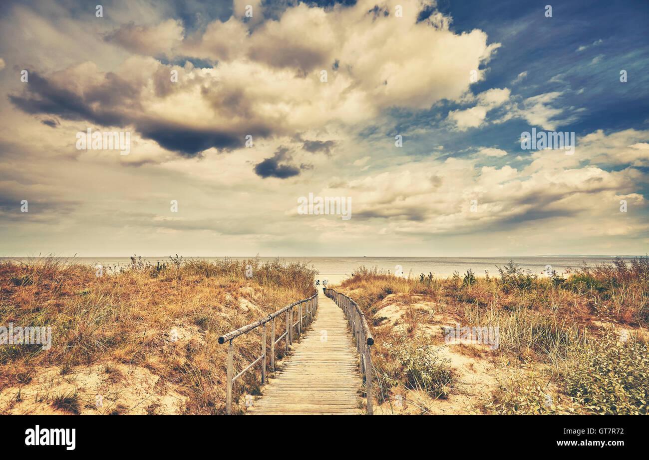 Retro getönten Holz Wanderweg führt zu einem Strand an einem bewölkten Tag. Stockbild