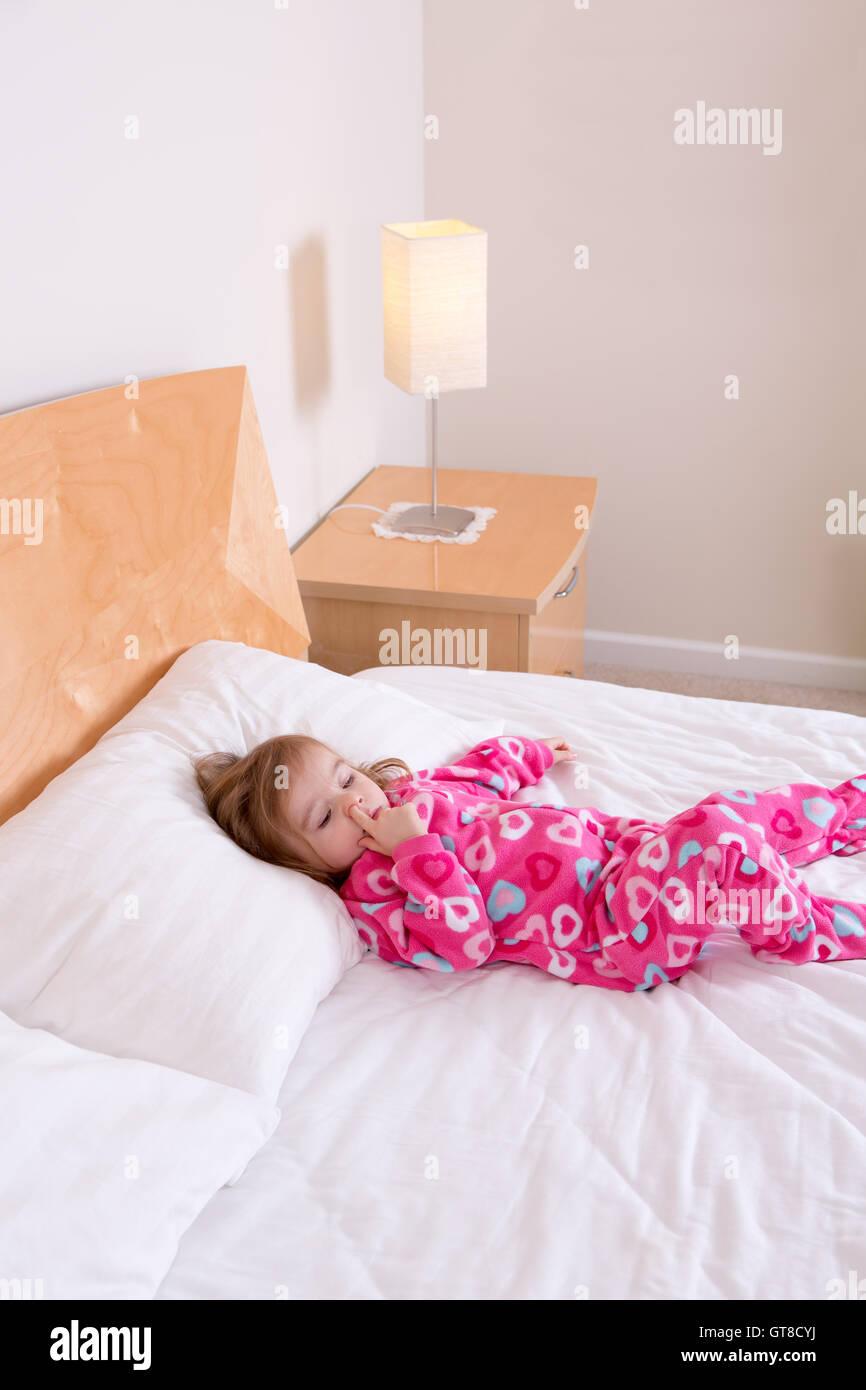 Entzückende kleine Mädchen in rosa Schlafanzug liegend ruhen auf ...