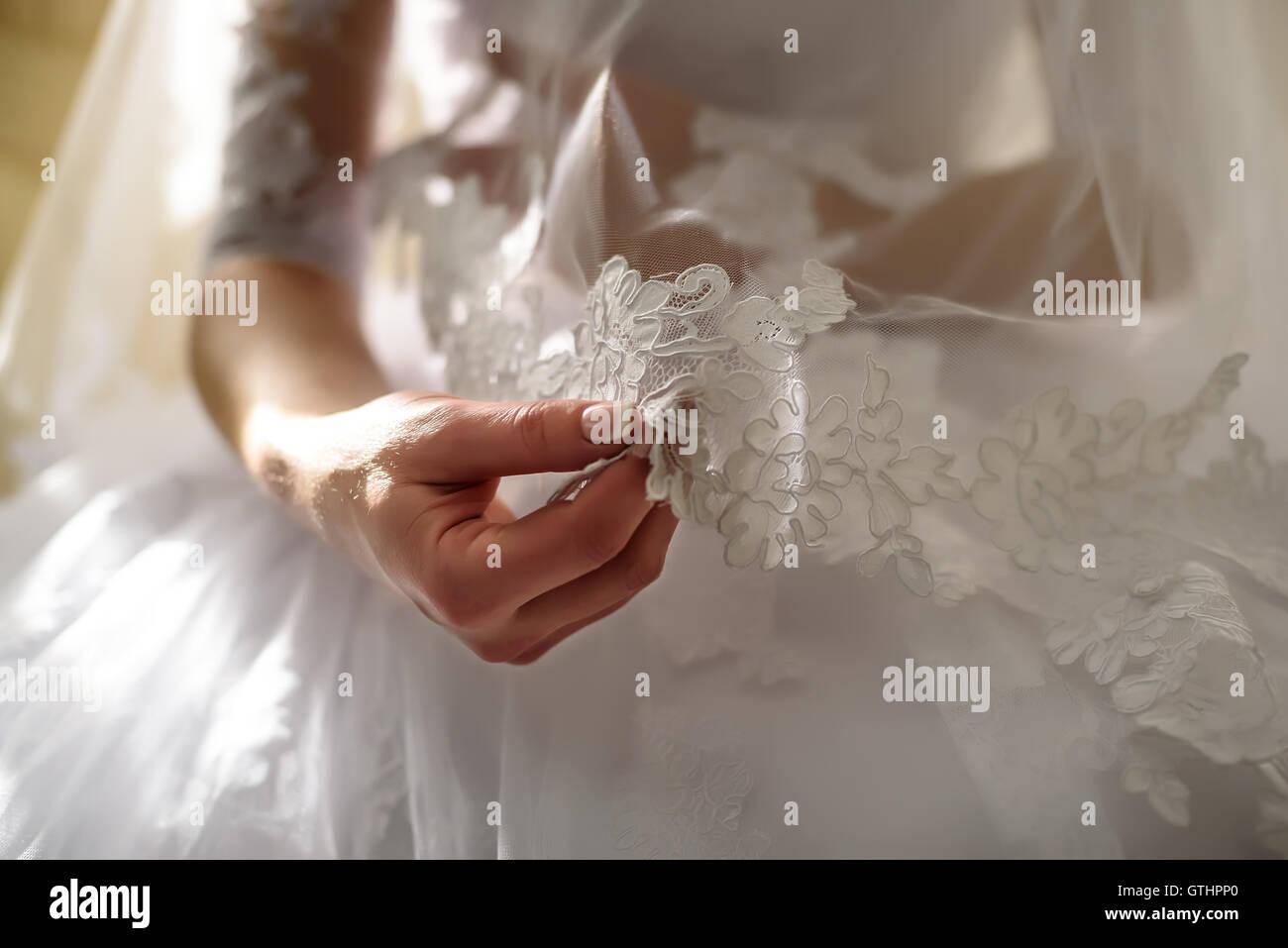 Die Braut hält in ihrer Hände und sieht Spitzenschals Stockbild