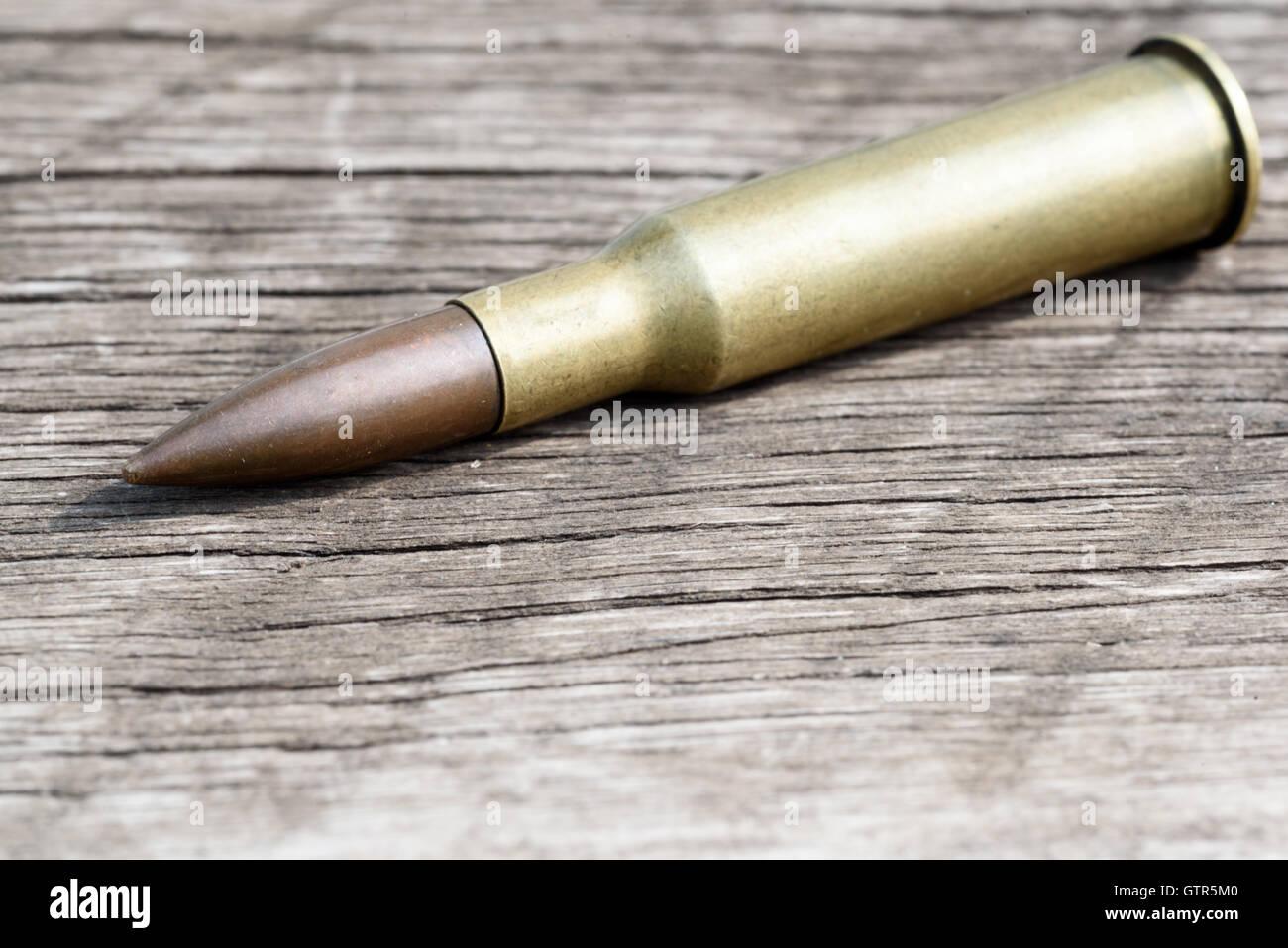Einzelne ungebrannten 7,62 mm Kugel und Messing Gehäuse liegende Diagonal auf eine gealterte Holzoberfläche. Stockbild
