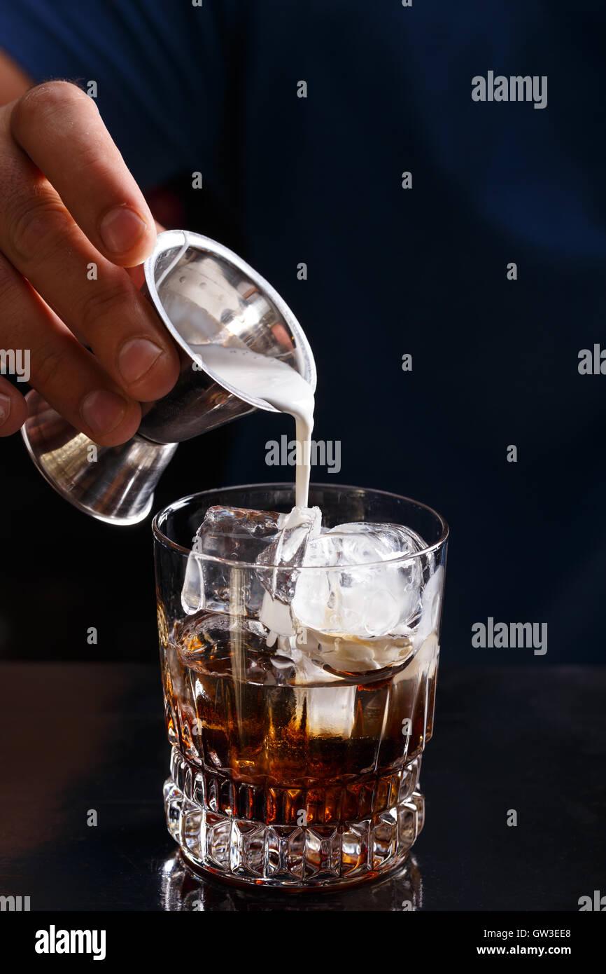 Barkeeper bereitet einen weißen russischen Cocktail im Nachtclub Stockbild
