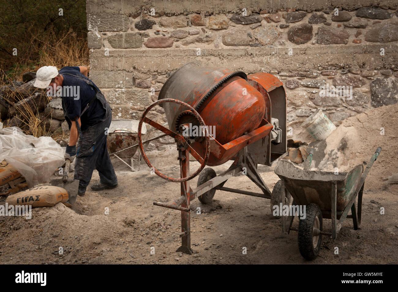 Albanischen Arbeiter mischt Zement auf Stellensuche Bau Reparatur einer Wand in Griechenland Stockfoto
