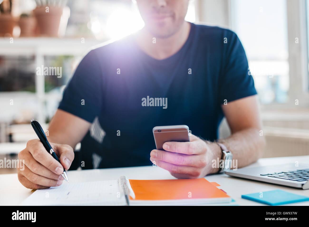 Geschäftsmann mit Handy während des Schreibens im Tagebuch. Schuss von Mannhände an seinem Schreibtisch Stockbild