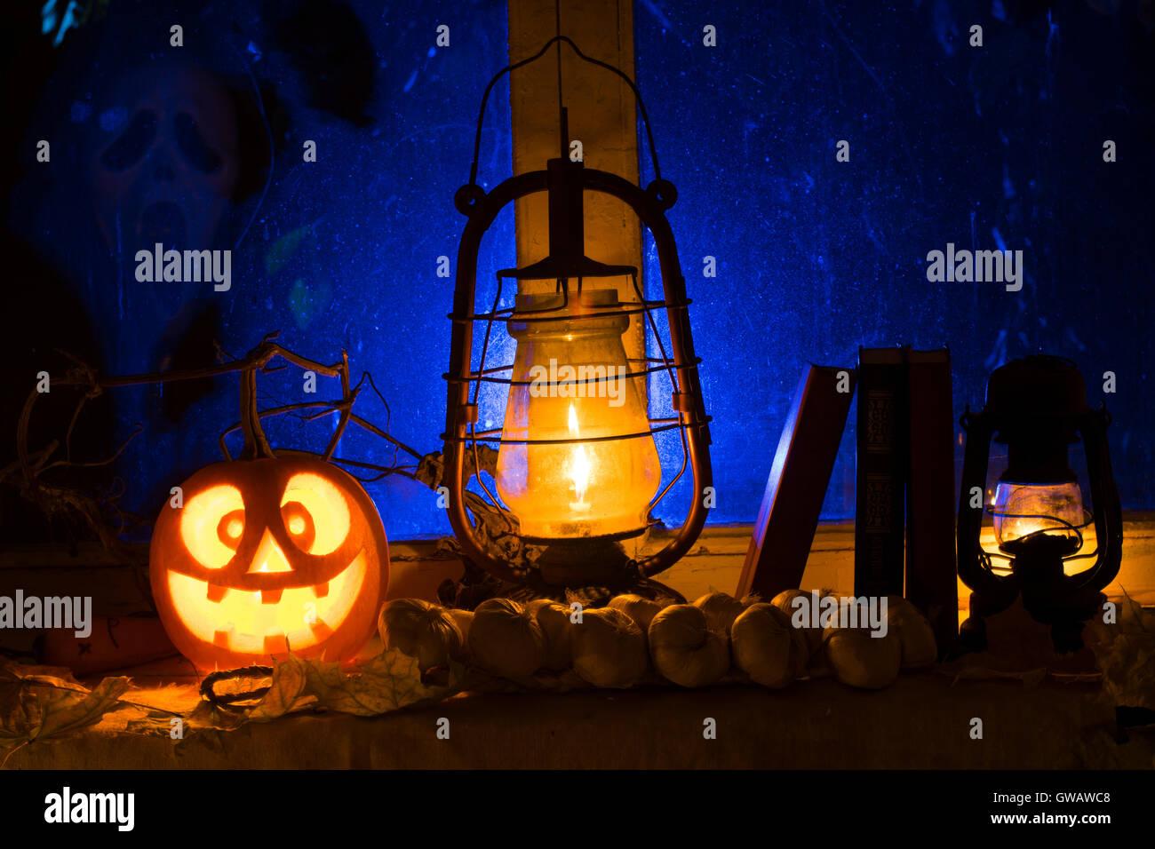 Fotomontage für Halloween von mad Kürbis, eine Öllampe und alte Bücher. Gegen eine alte Fenster Stockbild