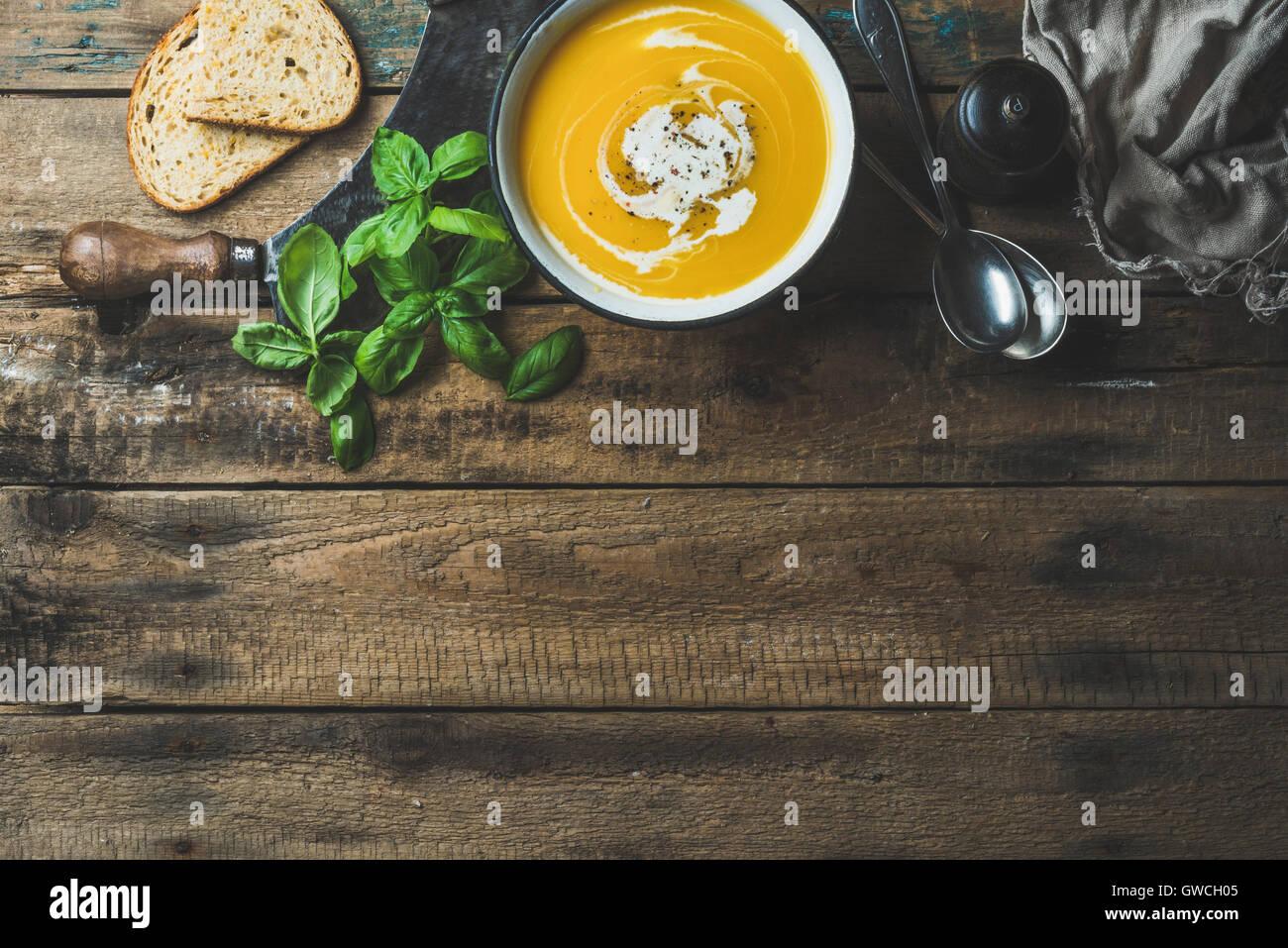 Kürbis Cremesuppe in Schüssel mit frischem Basilikum, Gewürze und gegrilltem Brot Scheiben über alten rustikalen Stockfoto