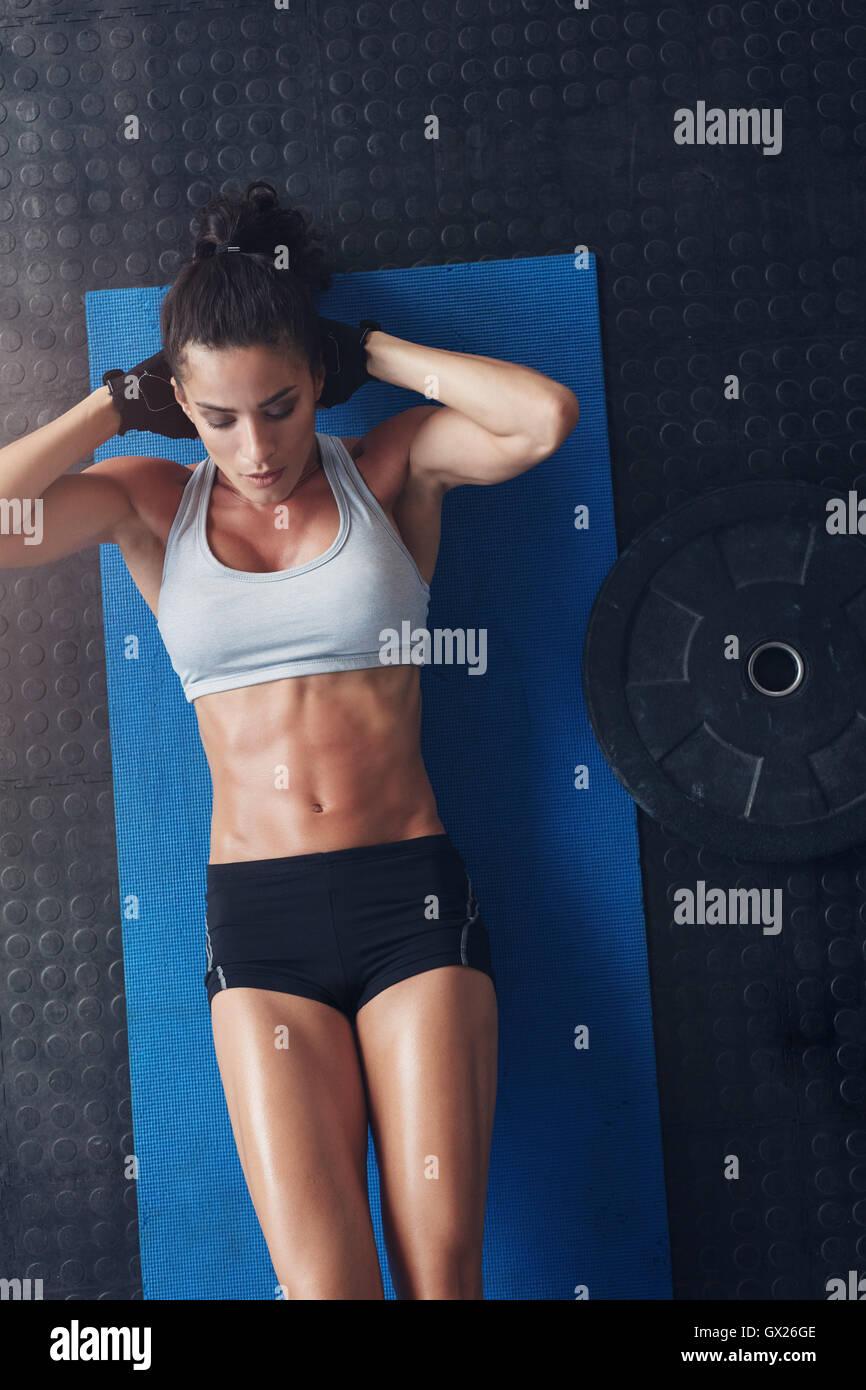 Draufsicht der muskulöse junge Frau tun Sit Ups auf eine Gymnastikmatte. Fitness-Frau liegend auf Yoga-Matte Stockbild
