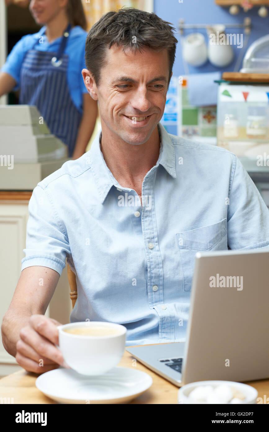 Mann In Coffee-Shop mit Laptop-Computer Stockbild