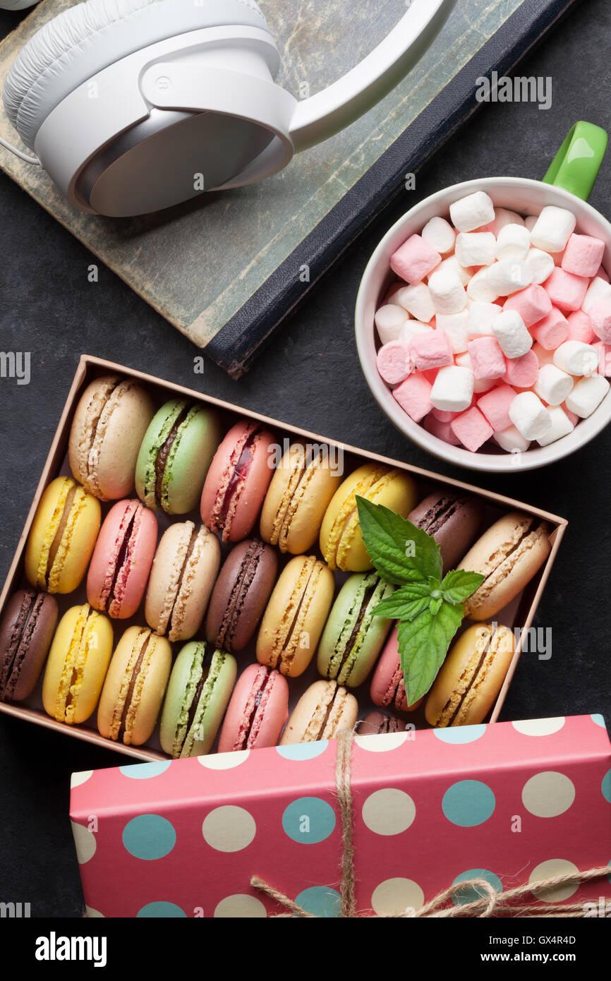 Bunte Macarons in einer Geschenkbox und Kopfhörer am Steintisch. Süßen Macarons. Ansicht von oben Stockbild