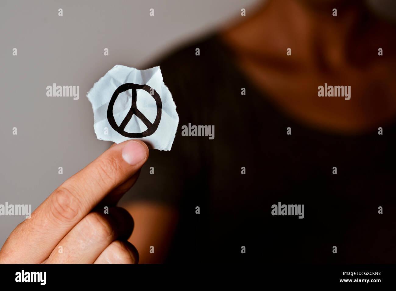 Nahaufnahme eines jungen Mannes zeigt ein Stück Papier mit ein Friedenssymbol es angesaugt Stockbild