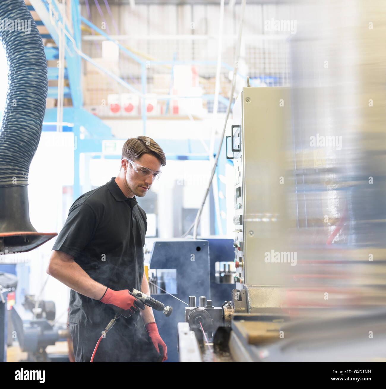 Arbeiter mit Maschine um Isolierung auf Kabel im Kabelwerk Stockbild