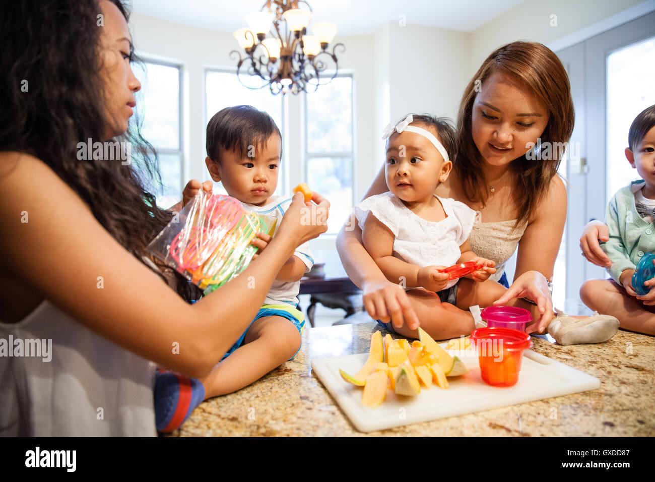 Frauen, die Fütterung baby Sohn und Tochter Obst auf Küchentisch Stockfoto