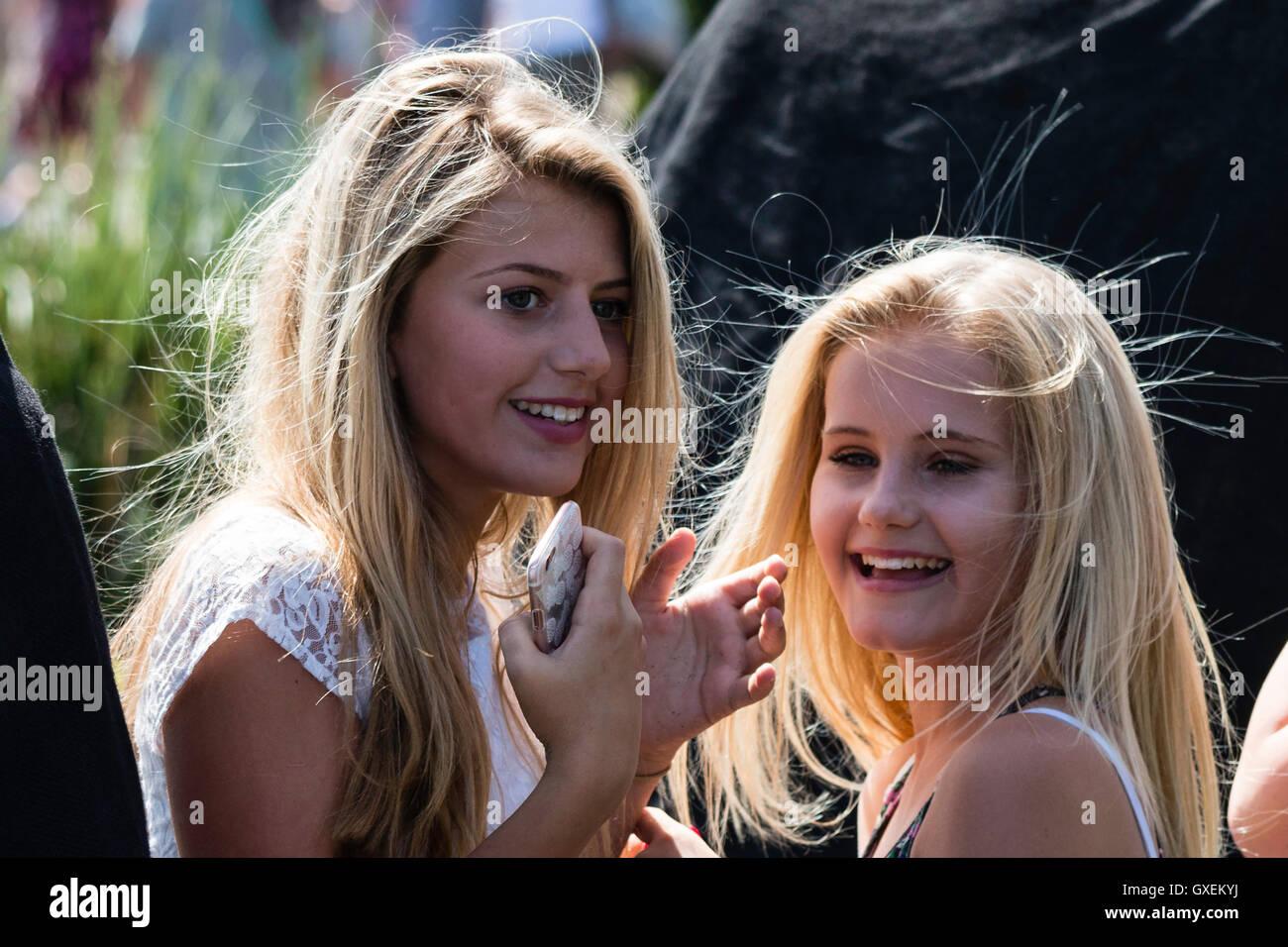 Zwei blonde Mädchen, 13-14 Jahre alt, beide drehten ihre Köpfe zu Gesicht beim Lachen, Sonnenlicht, ihr Stockbild