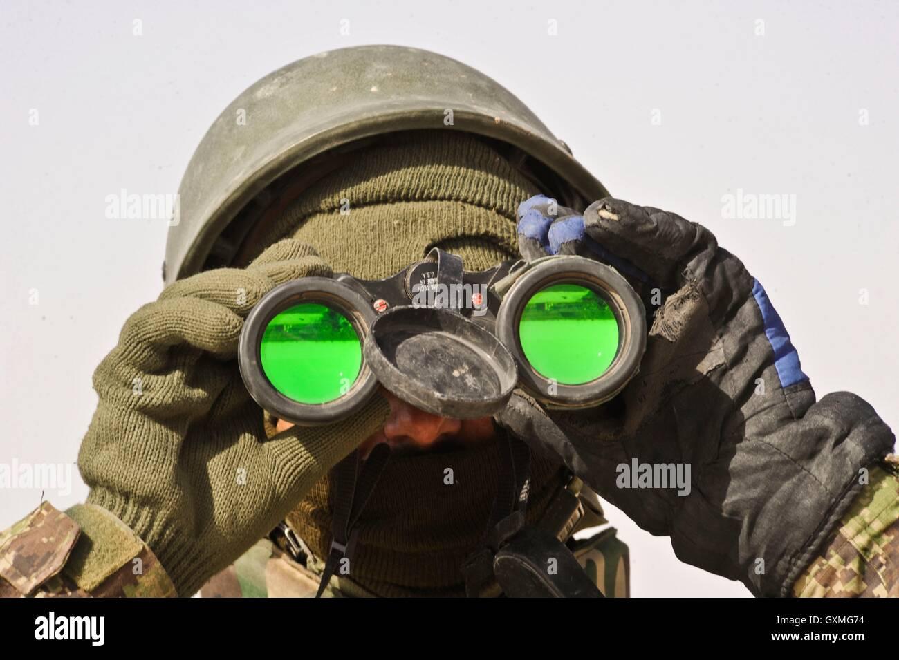 Afghan national army soldat schaut durch ein fernglas während einer