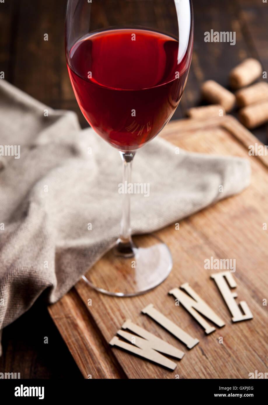 Glas Rotwein auf Holzbrett mit Küchentuch und mit Buchstaben und ...