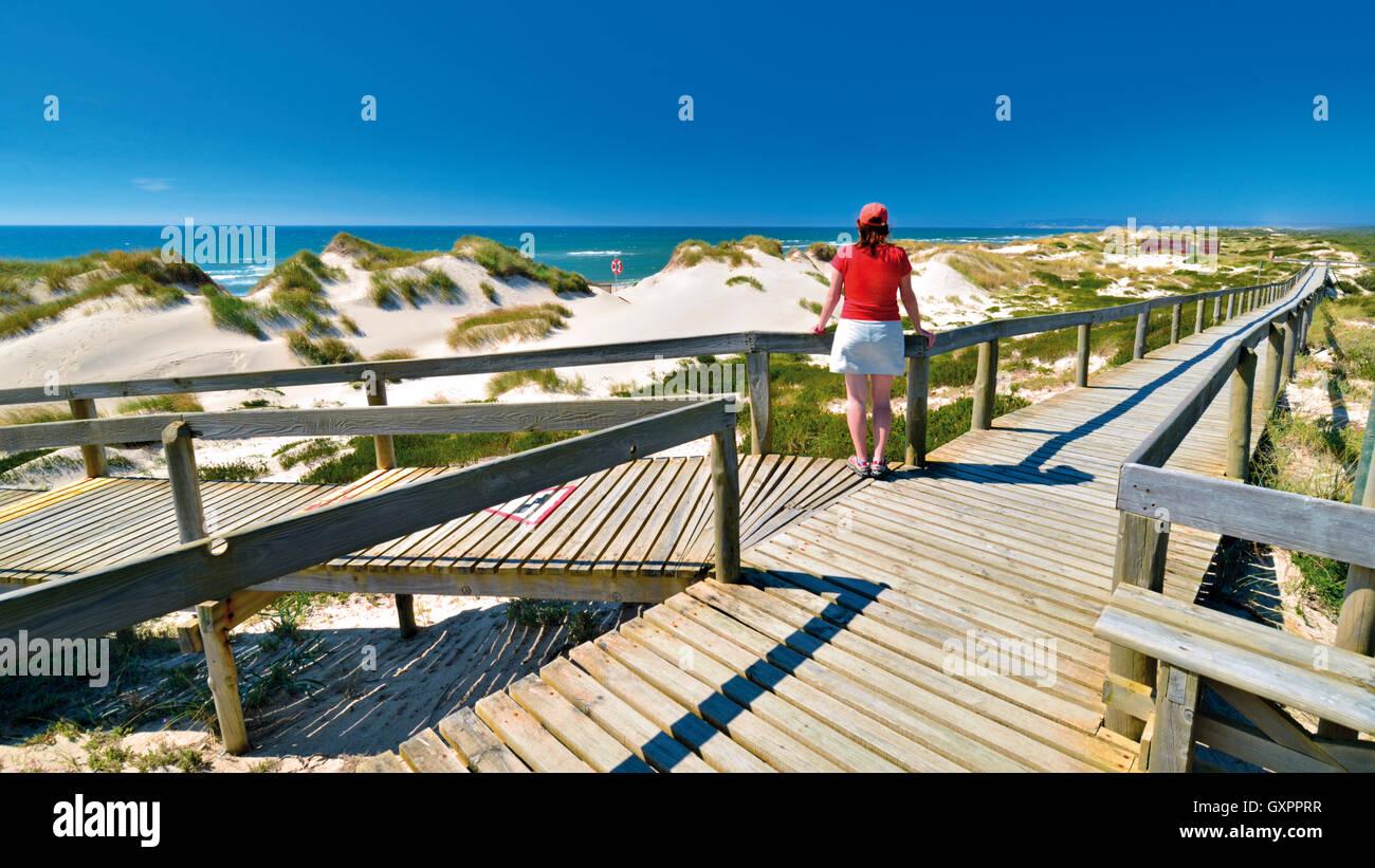 Portugal: Frau genießen Sie Strand und Meer Blick auf einem hölzernen Wanderweg in Praia de Comporta Stockbild