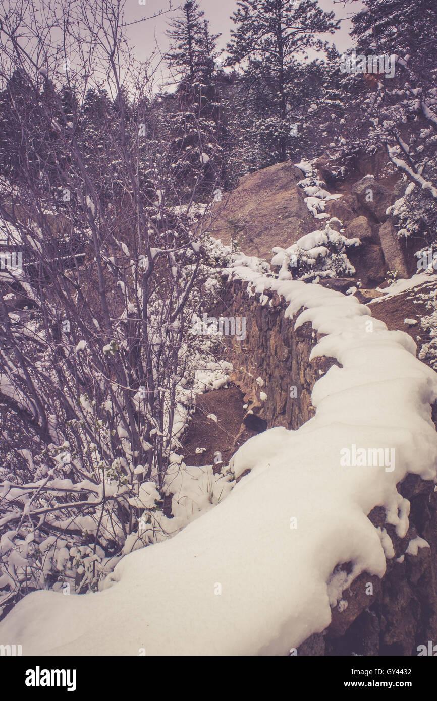 Steinmauer unter Schnee Stockbild