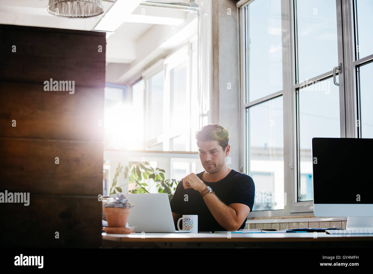 Schuss der junge Geschäftsmann arbeiten in modernen Arbeitsplatz. Männliche Unternehmer sitzt an seinem Stockbild