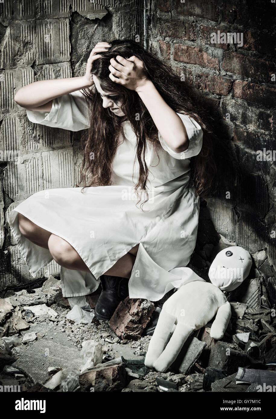 Horror-Stil gedreht: das seltsame verrückte Mädchen und ihre Puppe Mizzi Stockbild