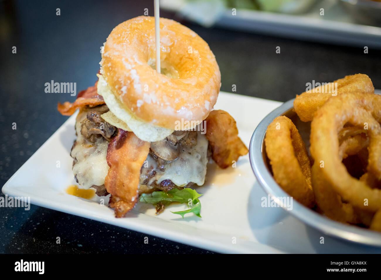 Ein Speck Donut Burger (Luther Burger) von Soda Idioten Restaurant in Edmonton, Alberta, Kanada. Stockbild