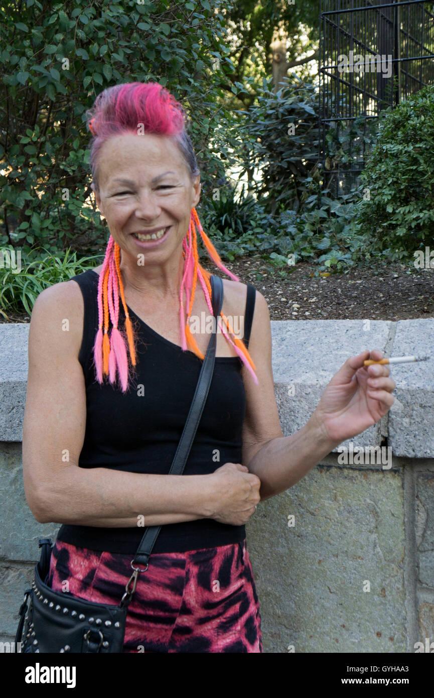 Eine junge Frau in ihren frühen Sechzigern mit bunten Haarverlängerungen. Im Union Square Park in New Stockbild