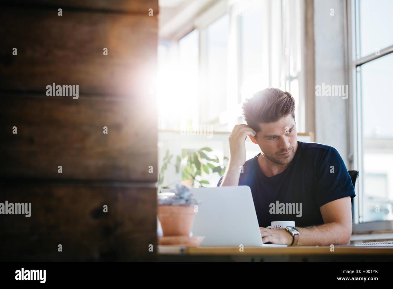 Junger Geschäftsmann mit Problemen und Stress im Büro. Mann an seinem Schreibtisch mit Laptop und schaut Stockbild