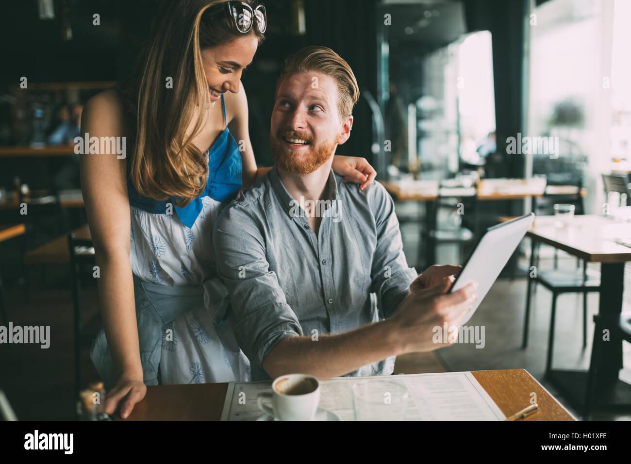 Frau und Mann Flirten im Café während der Diskussion Tablet-Inhalte Stockbild