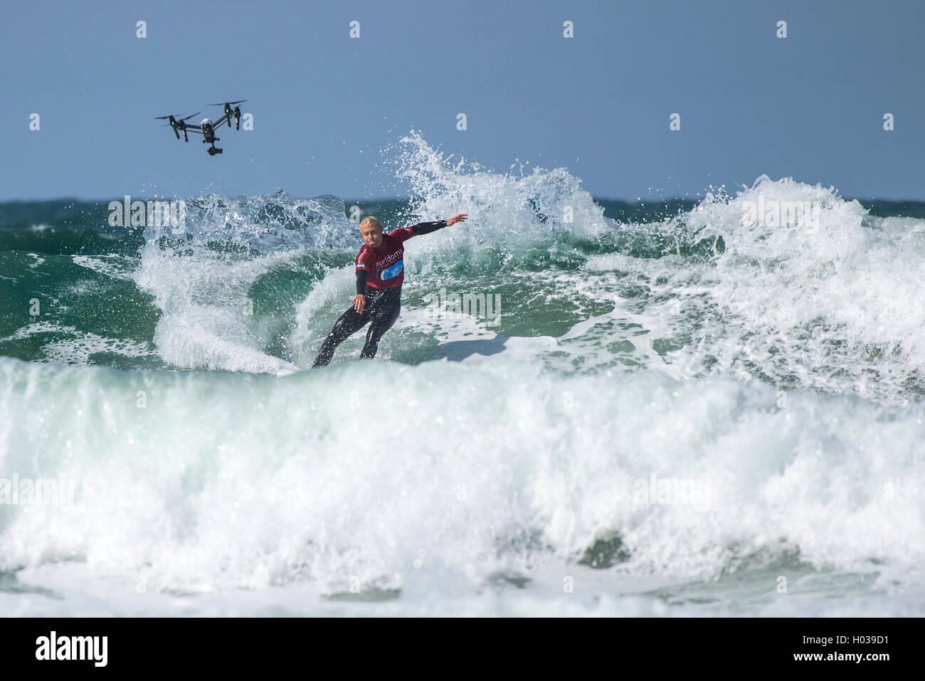 Eine Drohne filmt ein Konkurrent in Aktion bei der GB Inter Clubs Surfen Surfwettbewerb am Fistral in Newquay, Cornwall. Stockbild