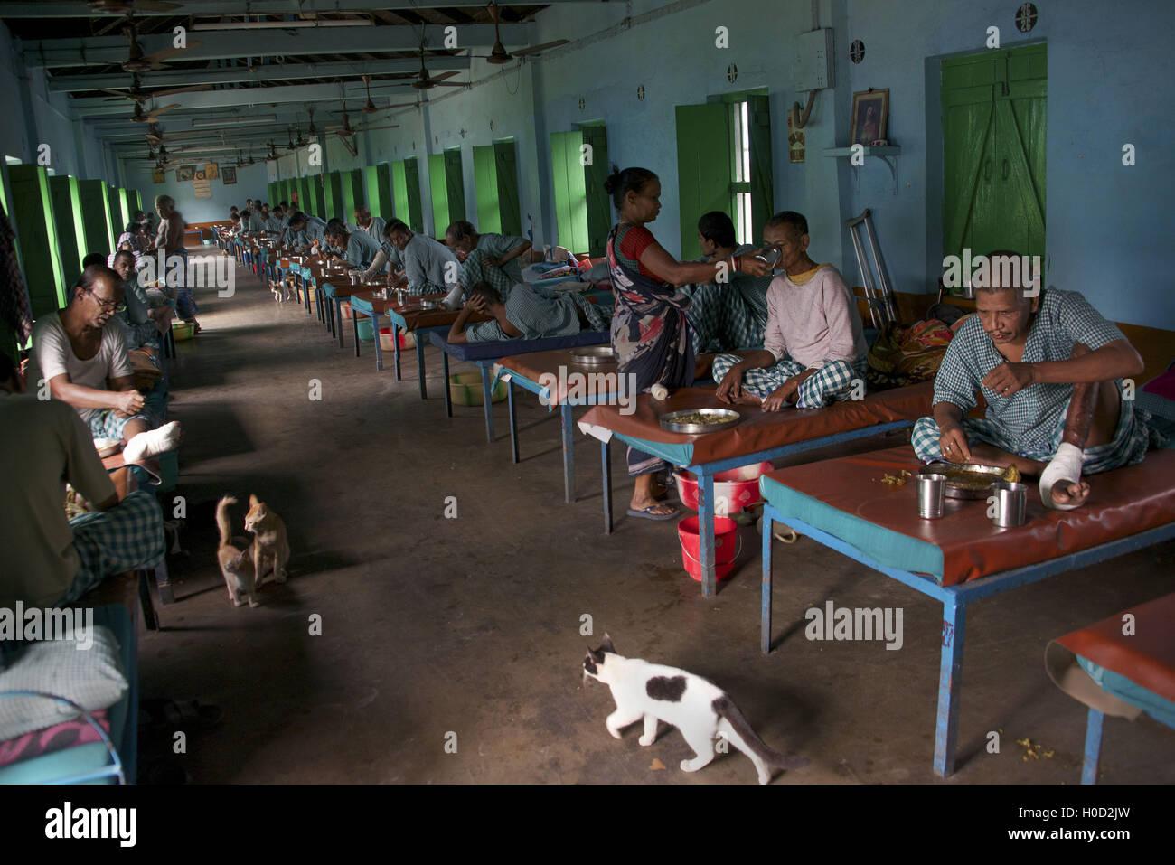Blick auf Mutter Teresa Lepra-Kolonie außerhalb Kolkata, Indien. Die Männer sind auf ihre Betten Mittagessen essen. Stockfoto