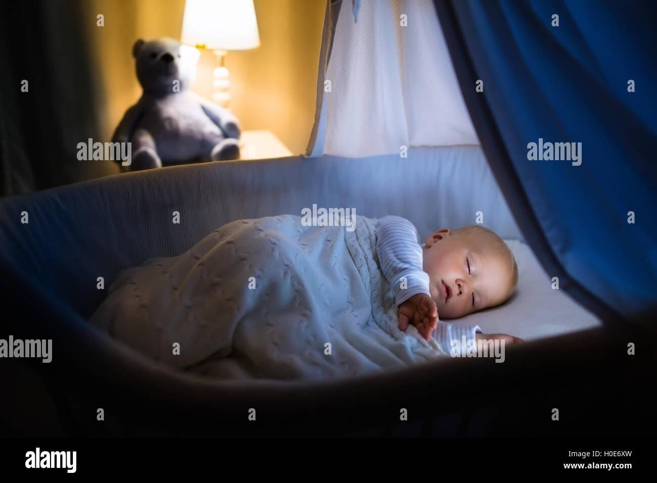Entzückende baby schlafen in der nacht in blau stubenwagen mit