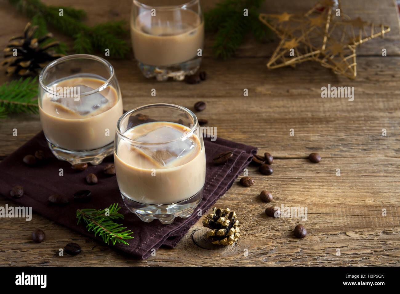 Irische Creme Kaffee-Likör mit Eis, Weihnachtsdekoration und Ornamente über rustikalen hölzernen Hintergrund - hausgemachte festliche trinken Stockfoto