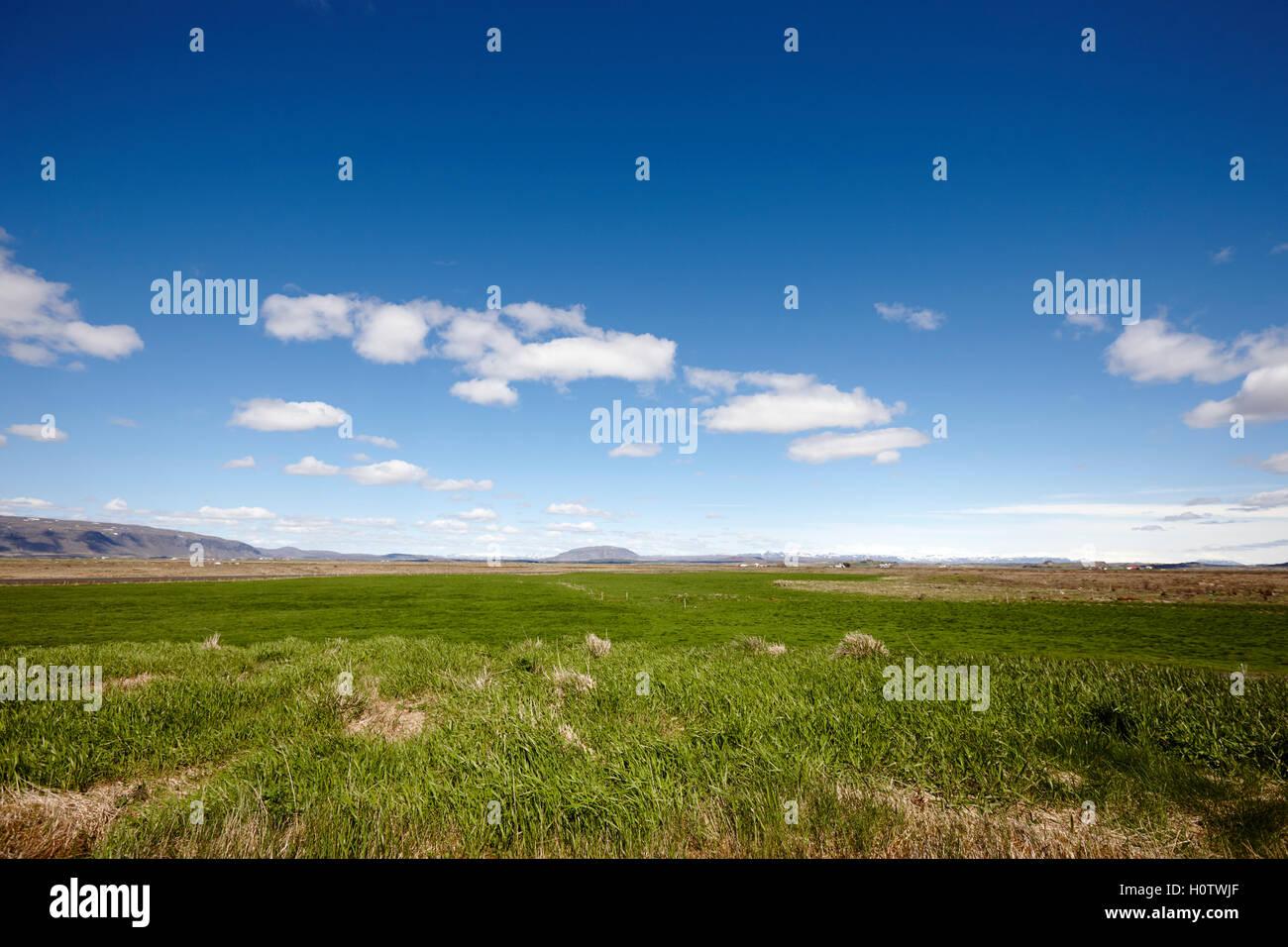 Wolken am blauen Himmel über einem üppigen fruchtbaren Tal von Ackerland in Island Stockbild