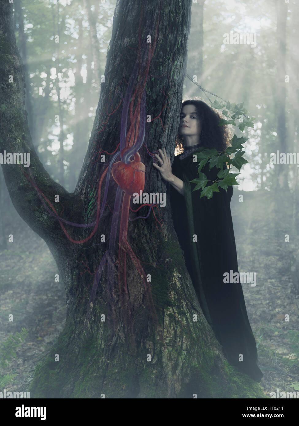Frau Druide im Wald hören den Herzschlag eines Baumes, künstlerische konzeptionelle Foto Illustration. Stockbild