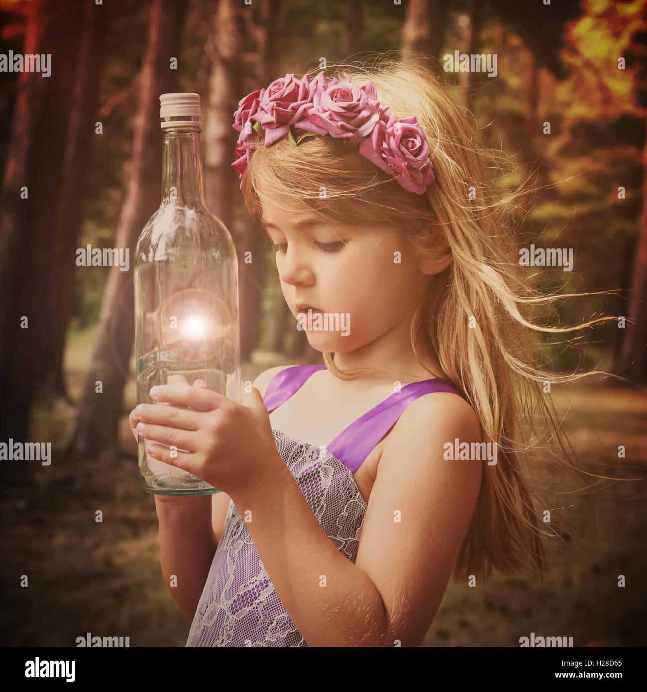 Ein kleine Fee Mädchen ist im Wald mit Blick auf eine magische Flasche für eine Vorstellung oder Phantasie Stockbild