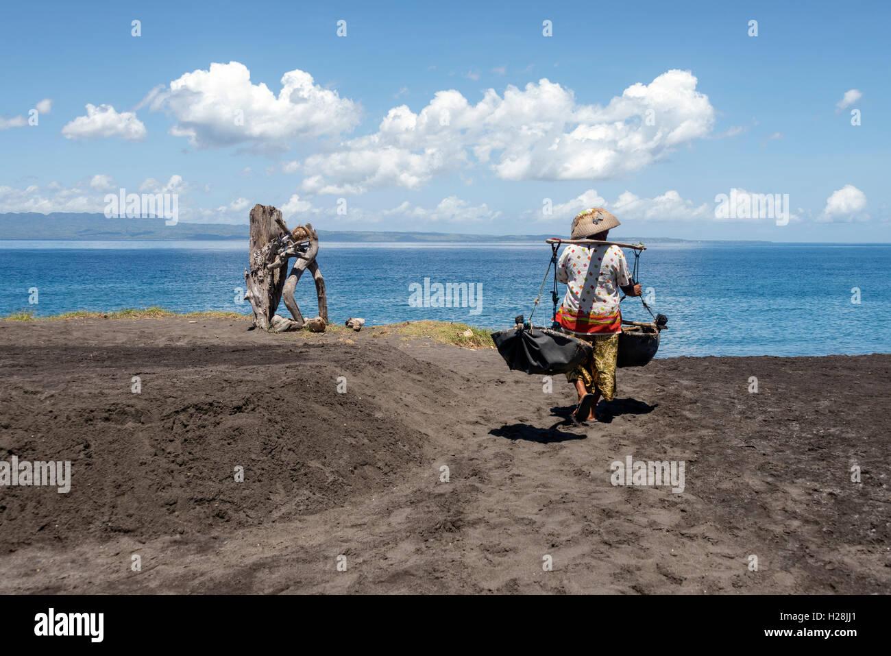 Frau, die ein Teku-Teku, Meerwasser, die später spritzte wird auf den Sand, um das Salz zu extrahieren zu sammeln. Stockbild