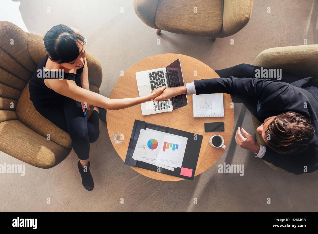 Draufsicht des jungen Kollegen Händeschütteln auf Deal. Charts und Laptop auf Tabelle, Statistiken und Stockbild