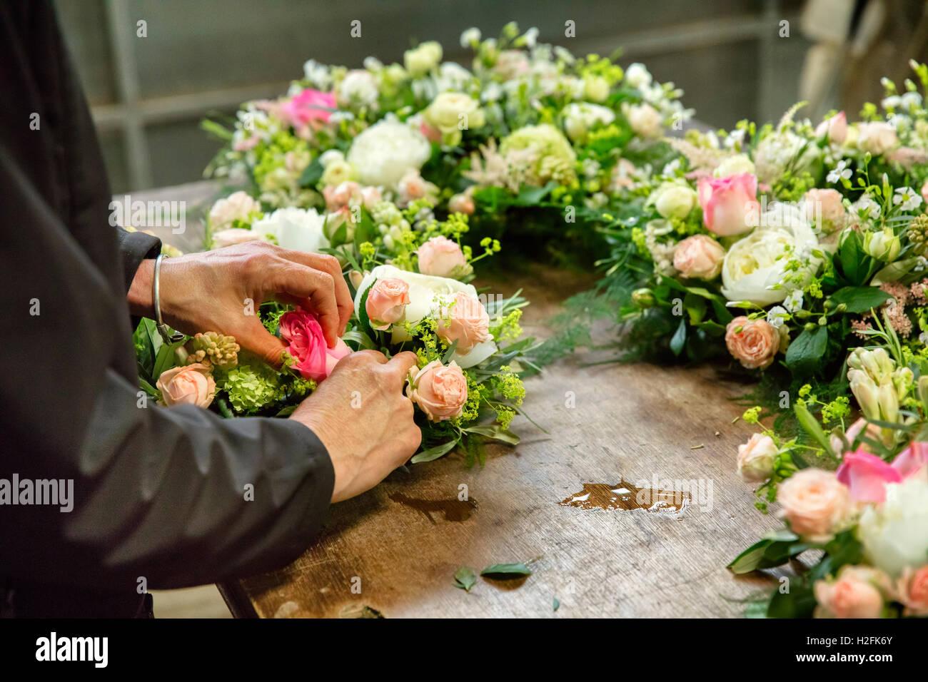 Kommerzielle Blumenbinden. Ein Blumengeschäft, eine Frau arbeitet an einem Blumenschmuck an einer Werkbank. Stockbild